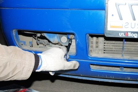 Откручиваем болт за нижней решеткой Volkswagen Golf IV